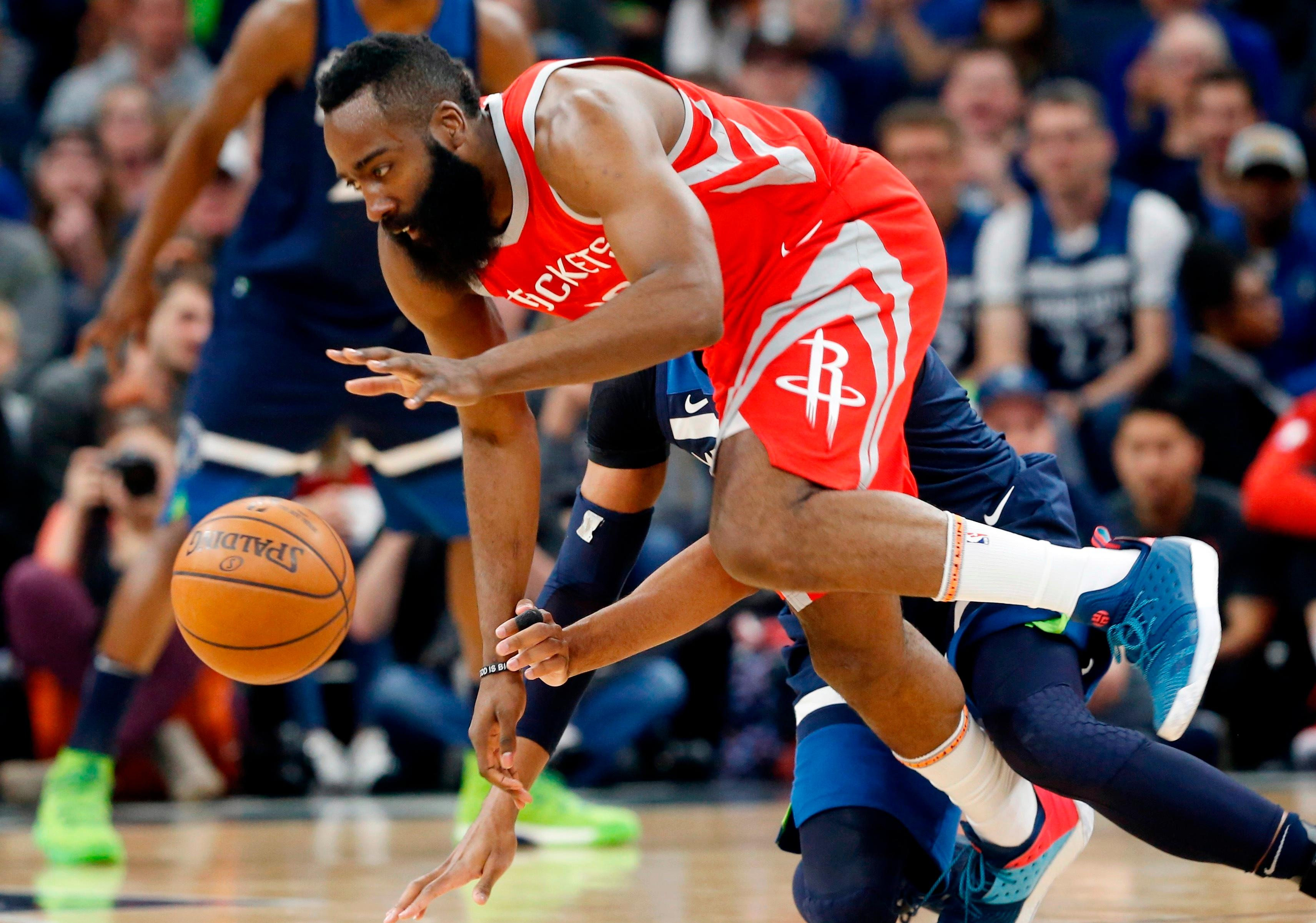 Houston Rockets' James Harden, front, and Minnesota Timberwolves' Taj Gibson become entangled while chasing the ball during the first half of Game 4 in an NBA basketball first-round playoff series Monday, April 23, 2018, in Minneapolis. (AP Photo/Jim Mone)