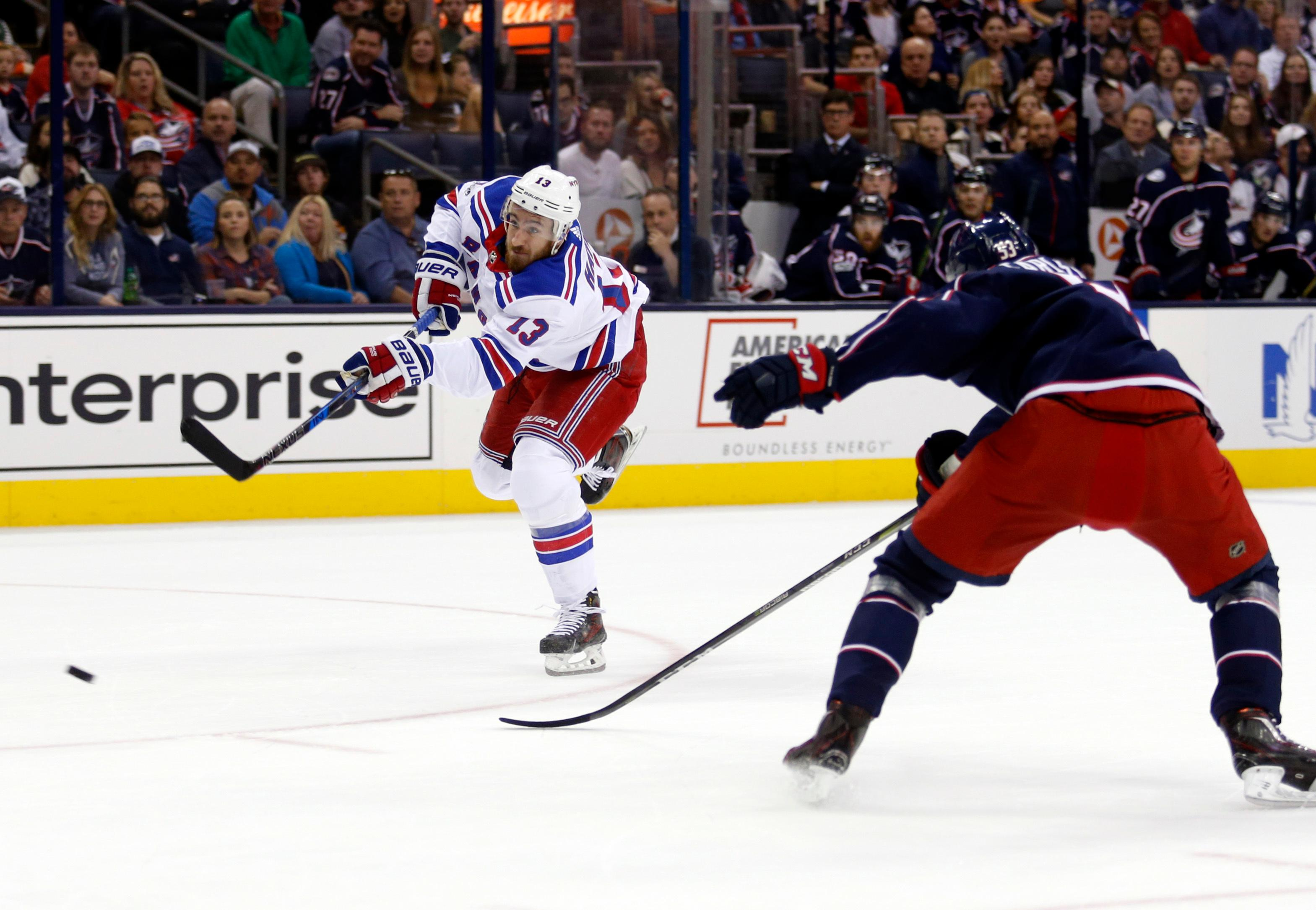 New York Rangers forward Kevin Hayes, left, shoots the puck in front of Columbus Blue Jackets defenseman Gabriel Carlsson, of Sweden, during the first period of an NHL hockey game in Columbus, Ohio, Friday, Oct. 13, 2017. Hayes scored on the play. (AP Photo/Paul Vernon)