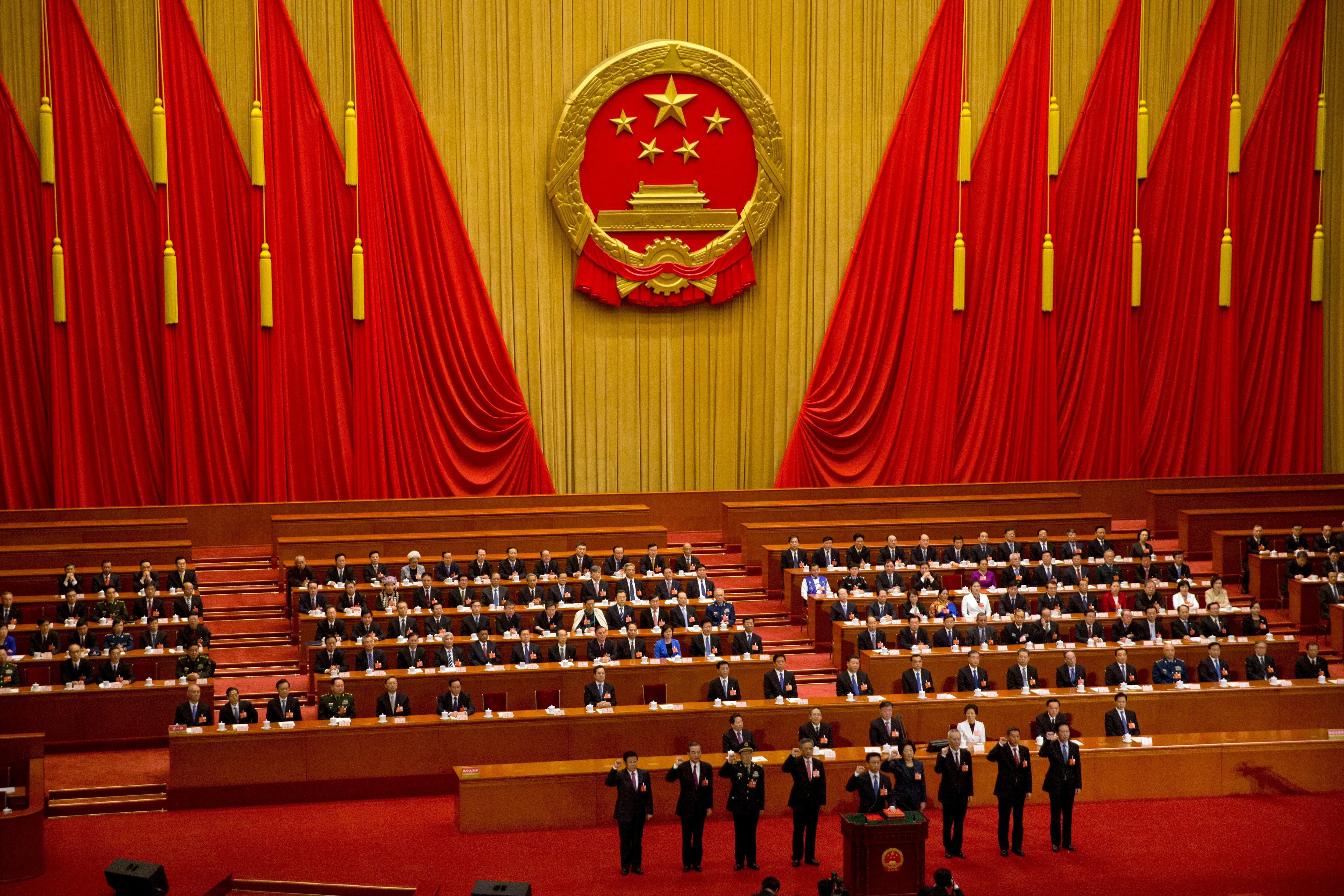 FILE - In this March 19, 2018, file photo, newly-appointed officials take the oath of office during a plenary session of China's National People's Congress (NPC) at the Great Hall of the People in Beijing. (AP Photo/Mark Schiefelbein, File)