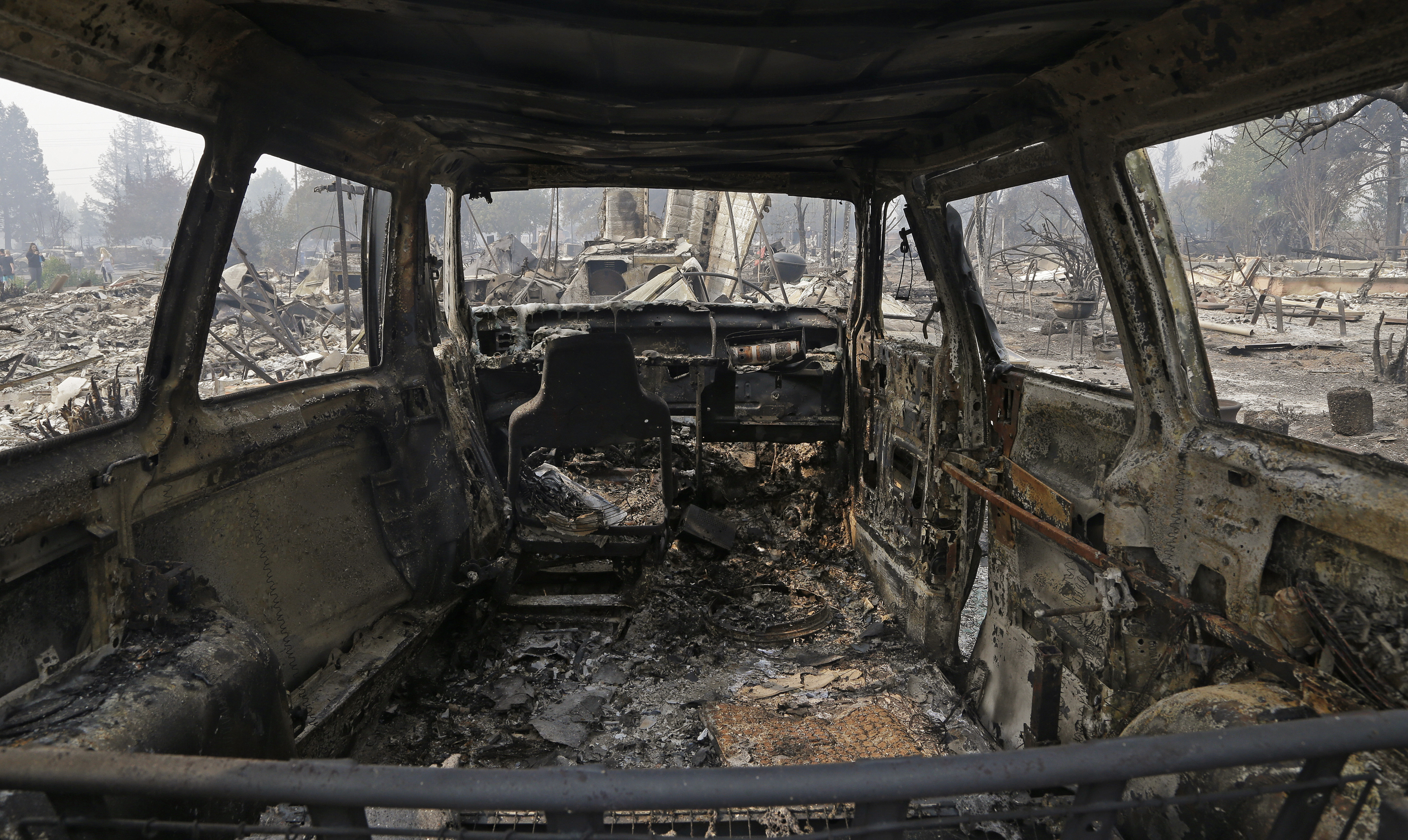 FILE - In this Oct. 10, 2017, file photo, a view from inside a parked car destroyed by fire in the Coffey Park area of Santa Rosa, Calif. An onslaught of wildfires across a wide swath of Northern California broke out almost simultaneously then grew exponentially, swallowing up properties from wineries to trailer parks and tearing through both tiny rural towns and urban subdivisions. (AP Photo/Ben Margot, File)