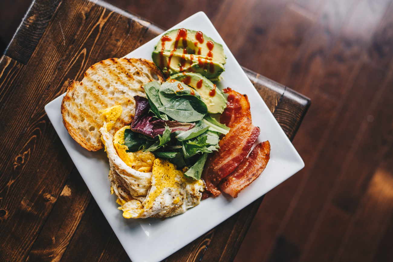 Price Hill Plate: scrambled eggs, thick cut bacon or goetta, sourdough toast, side of avocado, greens, and topped with a srircaha drizzle / Image: Catherine Viox // Published: 11.15.18