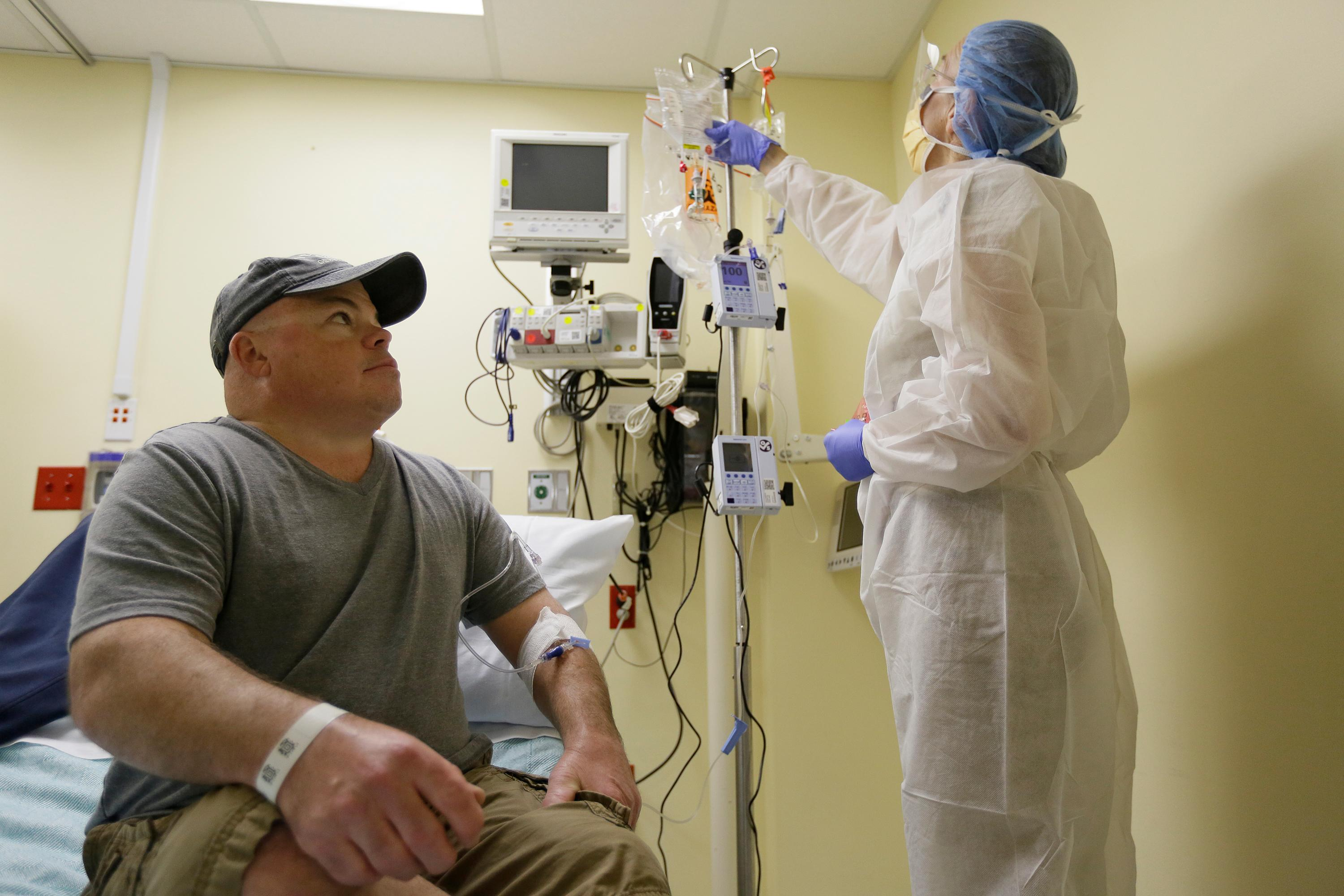 In this photo taken Monday, Nov. 13, 2017, Brian Madeux, 44, looks up at nurse practitioner Jacqueline Madde while receiving the first human gene editing therapy at the UCSF Benioff Children's Hospital in Oakland, Calif.  Madeux, who has a metabolic disease called Hunter syndrome, will receive billions of copies of a corrective gene and a genetic tool, through an IV,  to cut his DNA in a precise spot. (AP Photo/Eric Risberg)