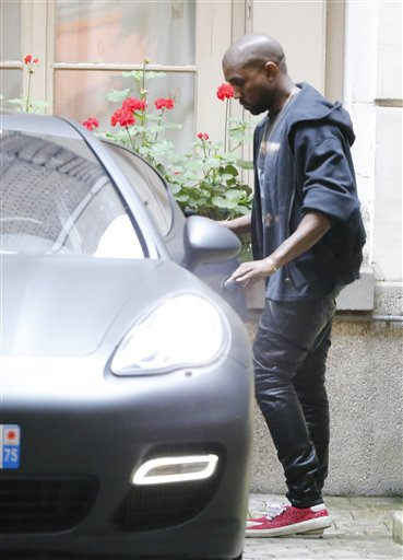 U.S rap singer Kanye West enters his car as he leaves a luxury shop in Paris, Tuesday, May 20, 2014.