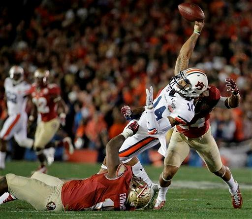 Auburn quarterback Nick Marshall (14) throws as he is hit by Florida State's Mario Edwards and Terrance Smith (24) during the first half of the NCAA BCS National Championship college football game Monday, Jan. 6, 2014, in Pasadena, Calif.